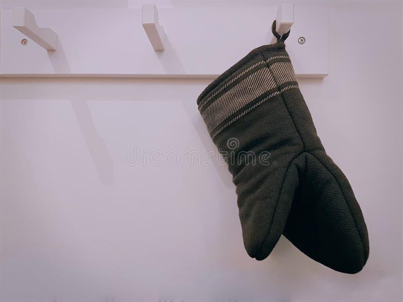 Ejecución negra del guante de la cocina en el gancho en la cocina fotos de archivo libres de regalías