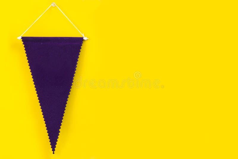 Ejecución púrpura oscura del banderín en la pared amarilla imagen de archivo libre de regalías