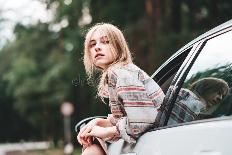 Ejecución que lleva de la mujer bonita del inconformista fuera de la ventanilla del coche que goza del camino forestal Estilo de  fotografía de archivo libre de regalías