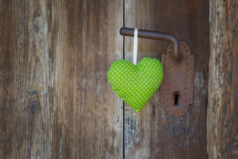 Ejecución verde en el tirador de puerta - ingenio de madera de la forma del corazón del fondo fotografía de archivo
