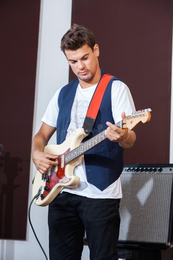 Ejecutante masculino que toca la guitarra eléctrica foto de archivo