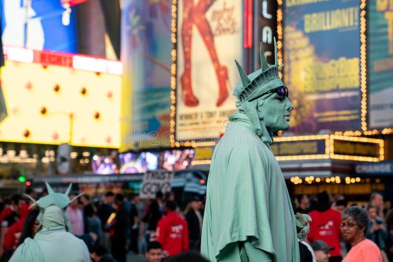 Ejecutantes de la calle vestidos como la estatua de la libertad imagen de archivo