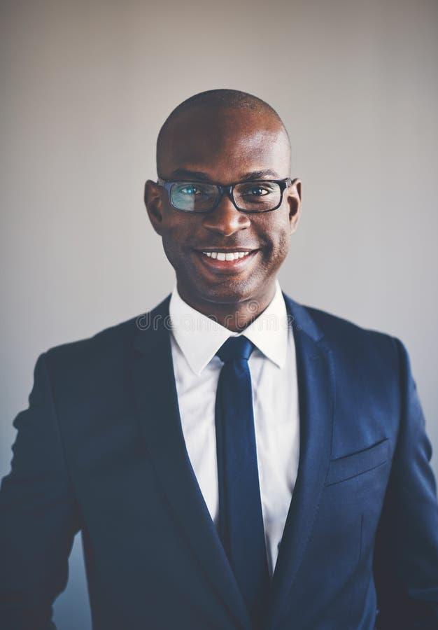 Ejecutivo africano joven sonriente que lleva un traje y los vidrios fotos de archivo libres de regalías