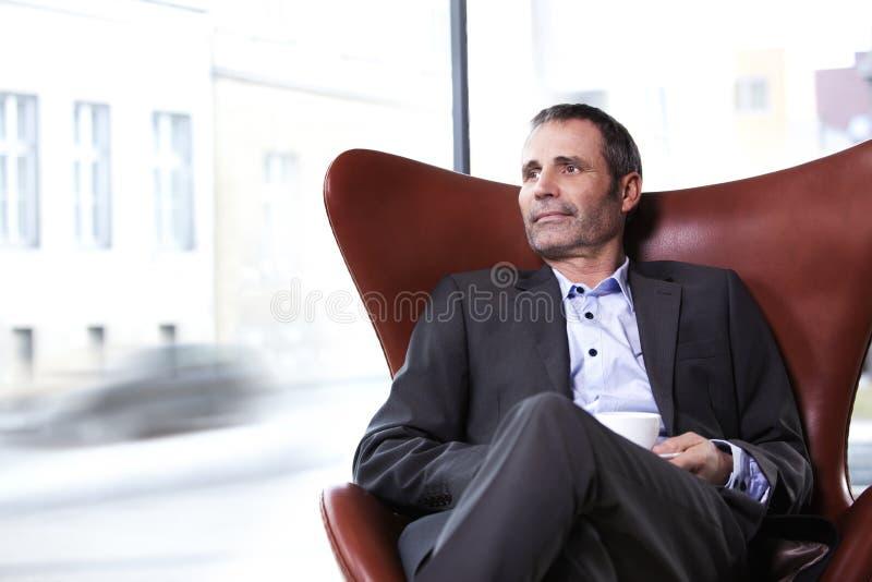 Ejecutivo de operaciones en silla roja que goza del café. fotos de archivo