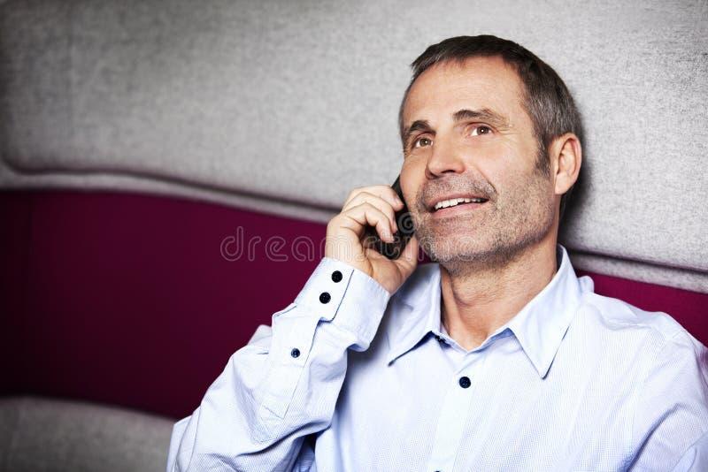 Ejecutivo de operaciones feliz que charla en el teléfono móvil. imagenes de archivo