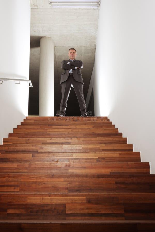 Ejecutivo de operaciones que se coloca en escalera de la oficina. imagenes de archivo
