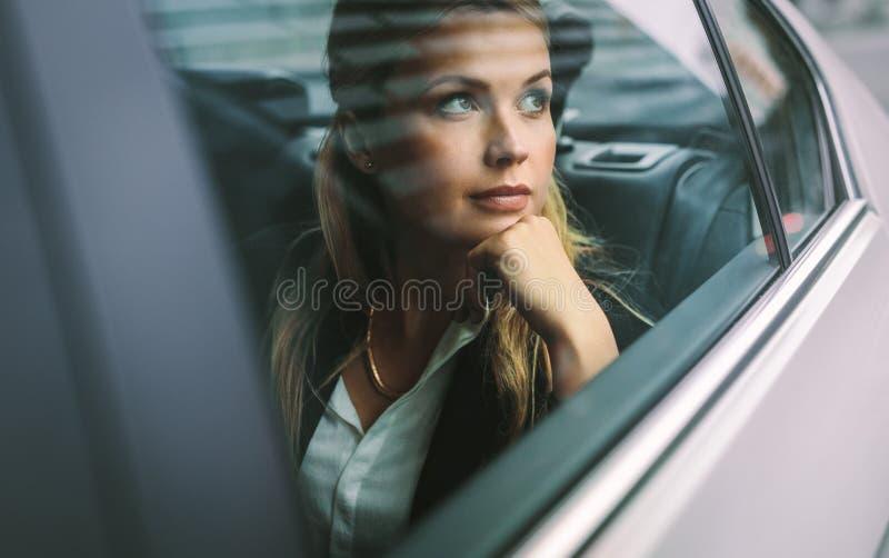 Ejecutivo de operaciones de sexo femenino que viaja por un taxi fotos de archivo libres de regalías