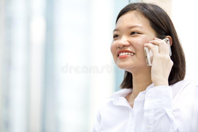 Ejecutivo de sexo femenino asiático joven que habla en el teléfono imagenes de archivo