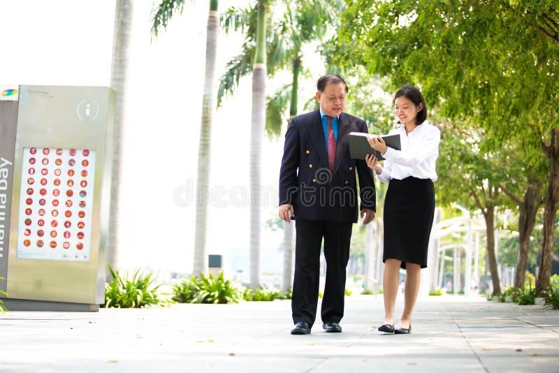 Ejecutivo de sexo femenino asiático joven y hombre de negocios mayor que caminan junto fotografía de archivo