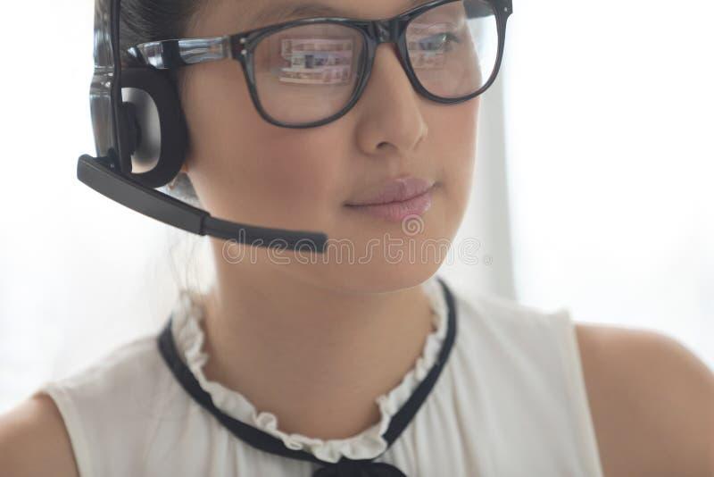 Ejecutivo de sexo femenino del servicio de atención al cliente con las auriculares que parecen ausentes en una oficina moderna foto de archivo