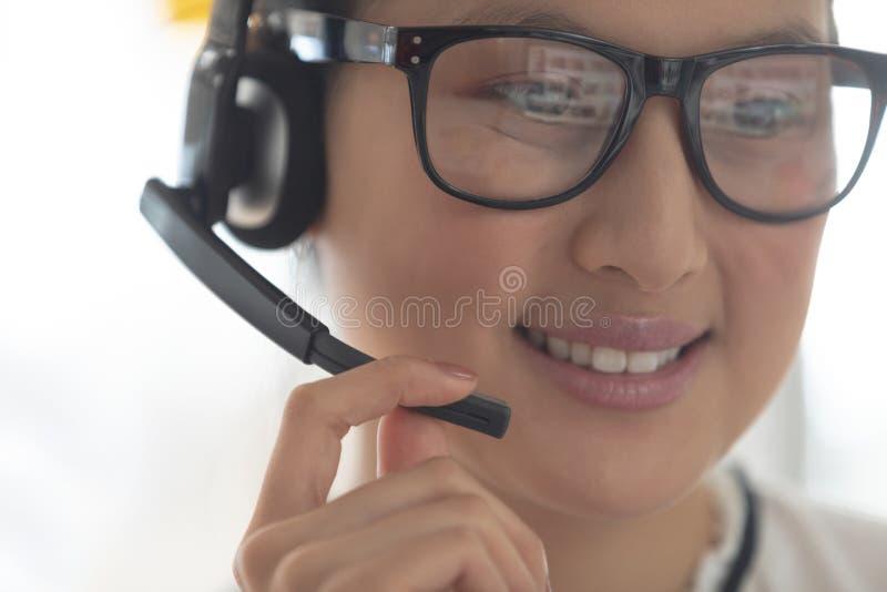 Ejecutivo de sexo femenino del servicio de atención al cliente que habla en las auriculares en una oficina moderna fotografía de archivo