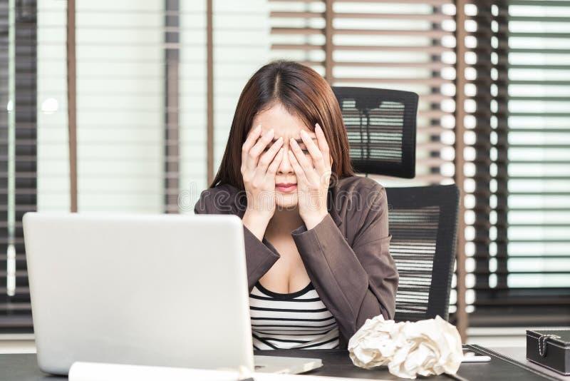 Ejecutivo de sexo femenino joven cansado que se sienta con las bolas de papel arrugadas a fotos de archivo libres de regalías