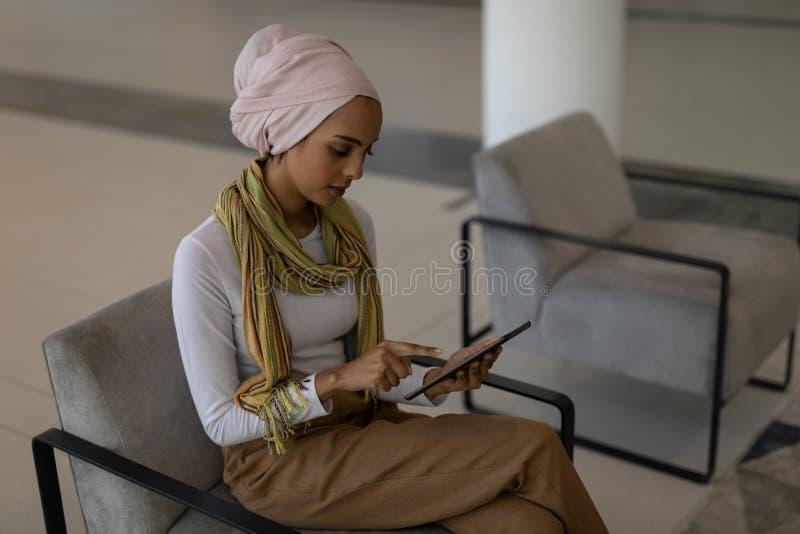 Ejecutivo de sexo femenino de la raza mixta joven que usa la tableta digital en oficina moderna imagen de archivo