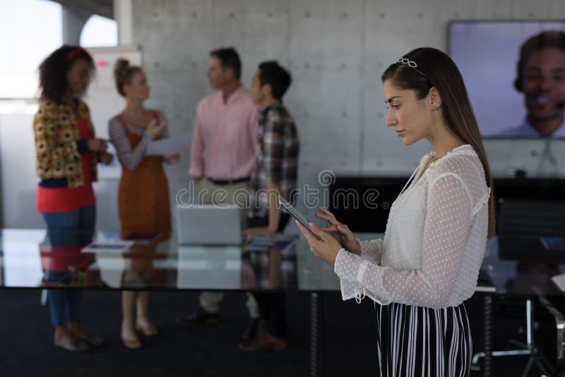 Ejecutivo de sexo femenino que usa la tableta digital en oficina foto de archivo libre de regalías