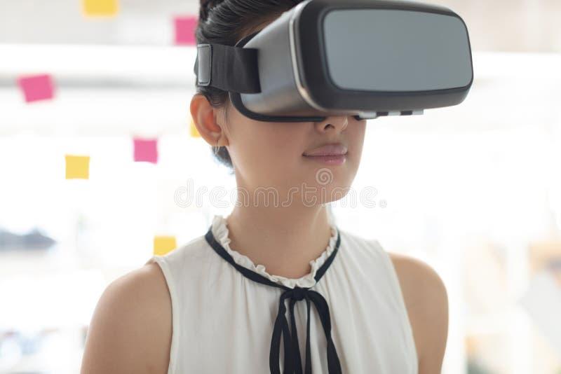 Ejecutivo de sexo femenino que usa las auriculares de la realidad virtual en una oficina moderna foto de archivo