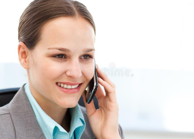 Ejecutivo de sexo femenino que usa su teléfono celular en su escritorio foto de archivo