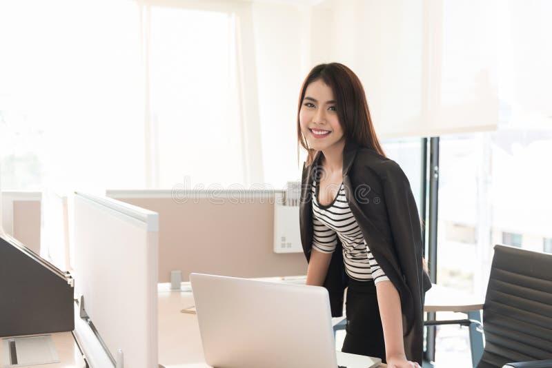 Ejecutivo de sexo femenino sonriente que se inclina en el escritorio en oficina foto de archivo