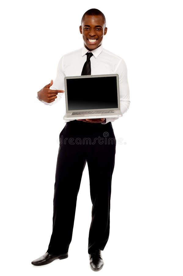 Ejecutivo de sexo masculino alegre que señala en la computadora portátil abierta imagen de archivo