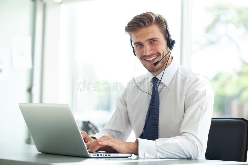 Ejecutivo de sexo masculino joven feliz de la atención al cliente que trabaja en oficina fotos de archivo libres de regalías