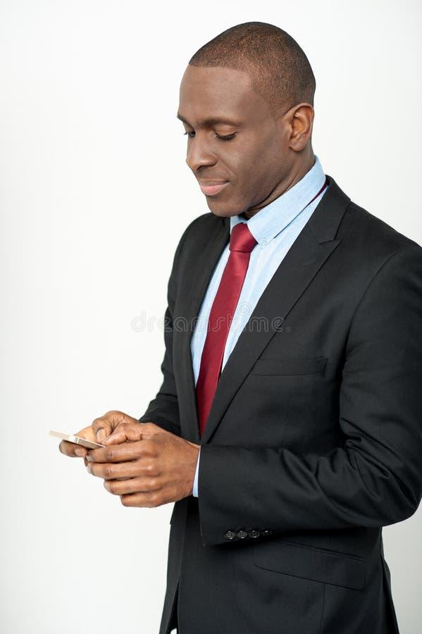 Ejecutivo de sexo masculino que usa su teléfono móvil imagen de archivo libre de regalías