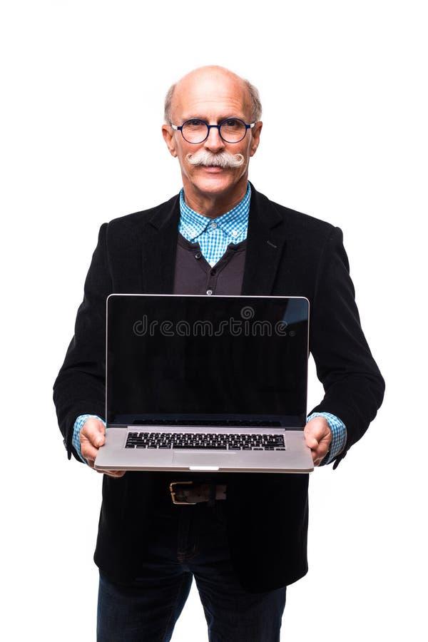 Ejecutivo del hombre mayor que se coloca con el ordenador portátil abierto aislado contra el fondo blanco foto de archivo