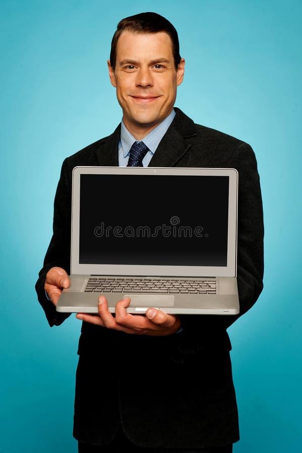 Ejecutivo empresarial que le muestra la computadora portátil fotografía de archivo