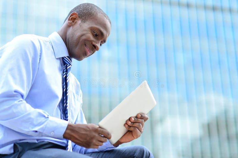Ejecutivo empresarial sonriente que usa una PC de la tableta imagen de archivo