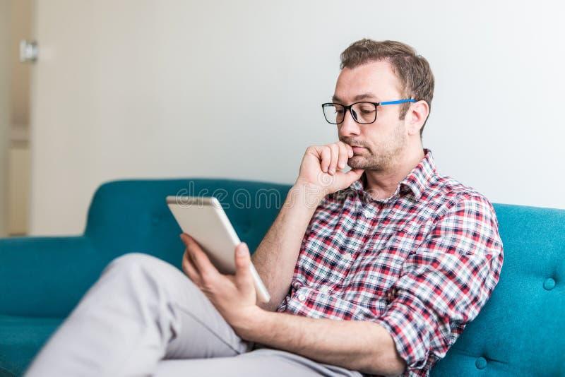 Ejecutivo moderno que sienta y que lleva a cabo el dispositivo de la tableta mientras que espera el encuentro a comenzar imágenes de archivo libres de regalías