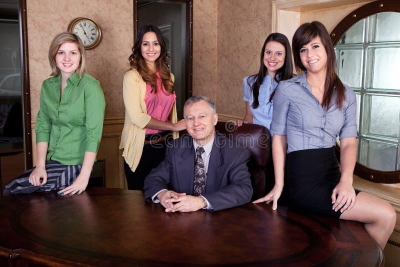 Ejecutivo 'senior' con las personas de mujeres jovenes imagen de archivo