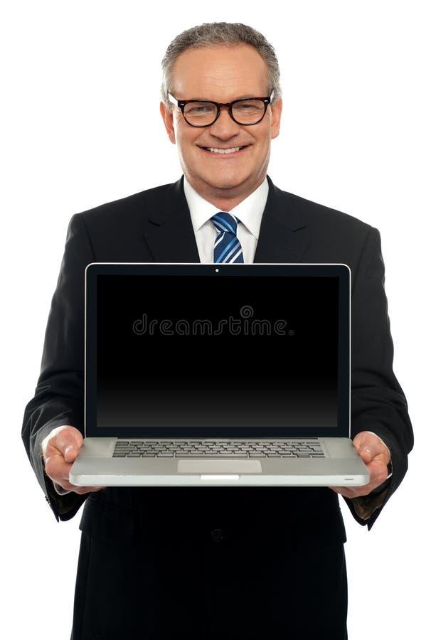Ejecutivo 'senior' que se coloca con la computadora portátil abierta imagen de archivo