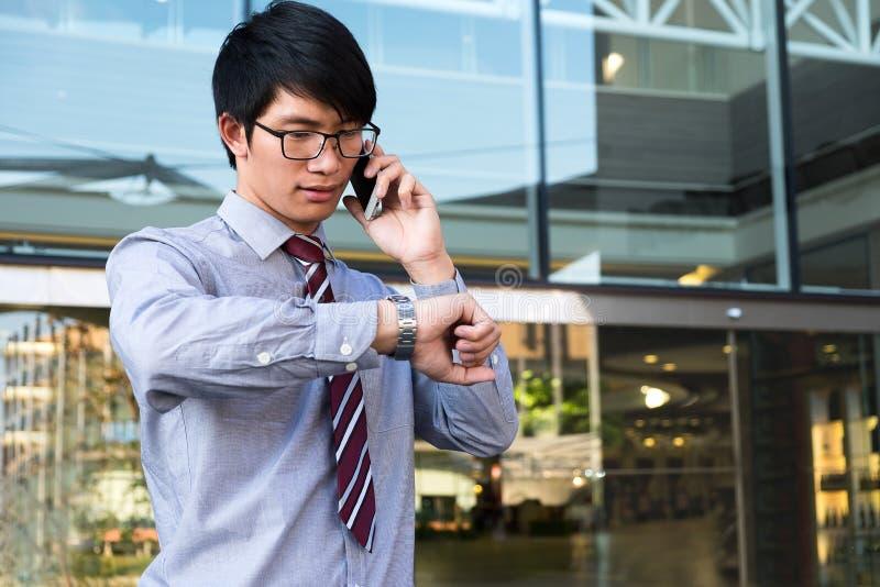 Ejecutivo a toda prisa, hombre de negocios que mira su reloj a mano, imagen de archivo