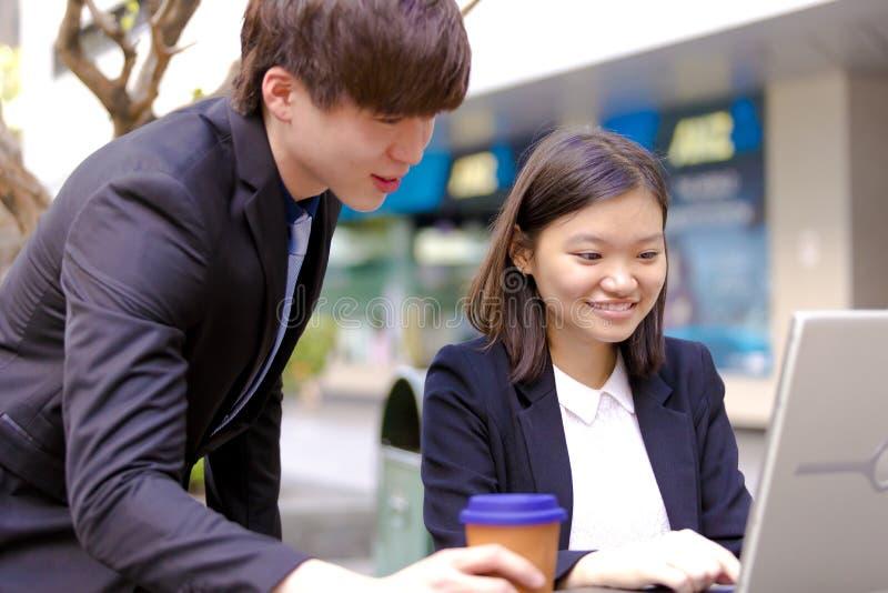 Ejecutivos de operaciones asiáticos jovenes en la discusión usando la PC de la tabla foto de archivo