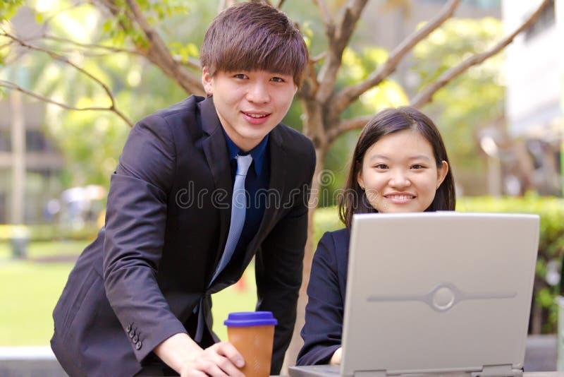 Ejecutivos de operaciones asiáticos jovenes en la discusión usando la PC de la tabla fotos de archivo