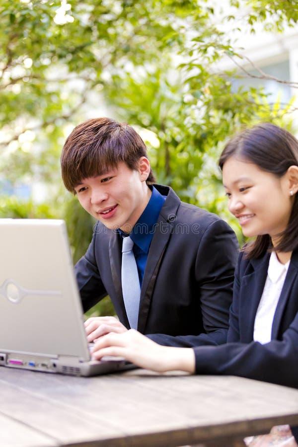 Ejecutivos de operaciones asiáticos jovenes en la discusión usando la PC de la tabla fotos de archivo libres de regalías
