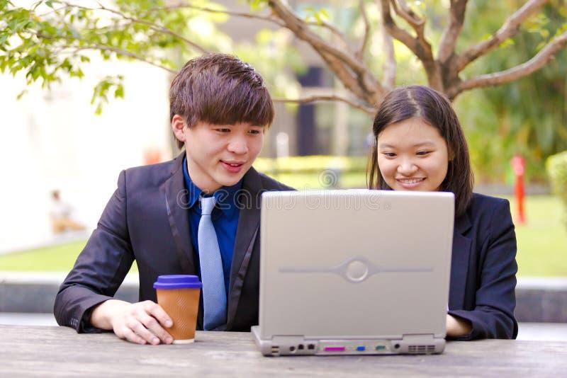 Ejecutivos de operaciones asiáticos jovenes en la discusión usando la PC de la tabla imagenes de archivo