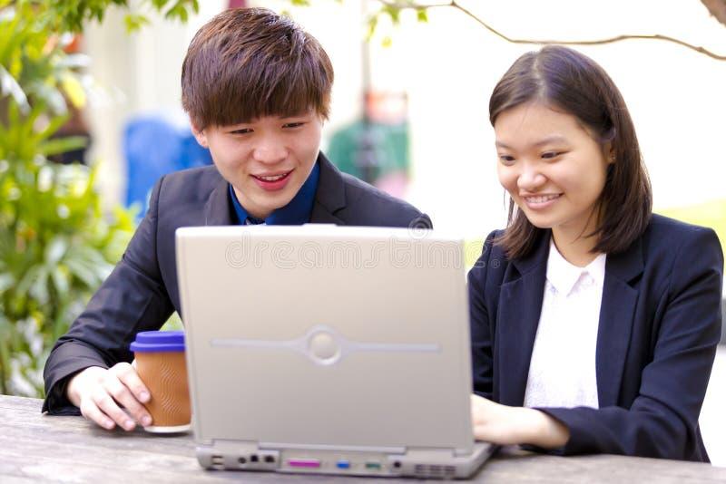 Ejecutivos de operaciones asiáticos jovenes en la discusión usando la PC de la tabla imagen de archivo