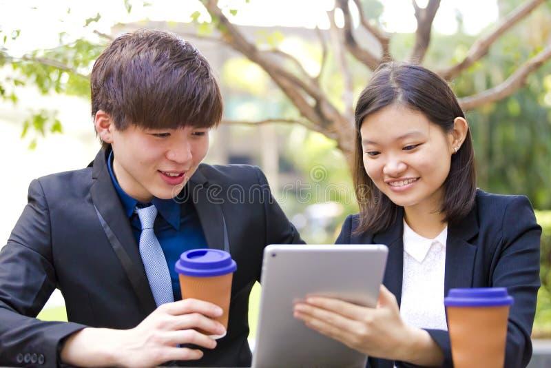 Ejecutivos de operaciones asiáticos jovenes en la discusión usando la PC de la tabla fotografía de archivo