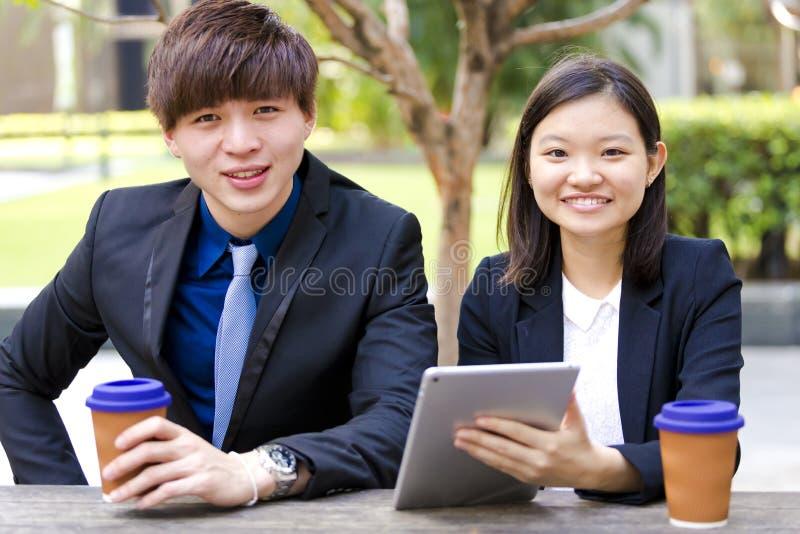 Ejecutivos de operaciones asiáticos jovenes en la discusión usando la PC de la tabla imagen de archivo libre de regalías