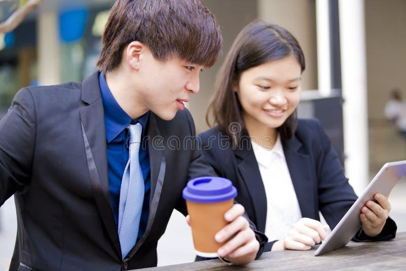 Ejecutivos de operaciones asiáticos jovenes en la discusión usando la PC de la tabla imágenes de archivo libres de regalías