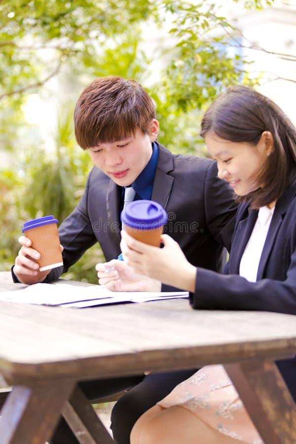 Ejecutivos de operaciones asiáticos jovenes que beben el café en la discusión fotografía de archivo libre de regalías