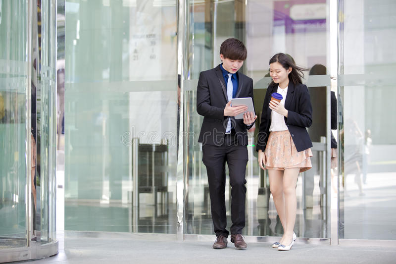 Ejecutivos de operaciones asiáticos jovenes que caminan y que discuten con la tableta imagenes de archivo