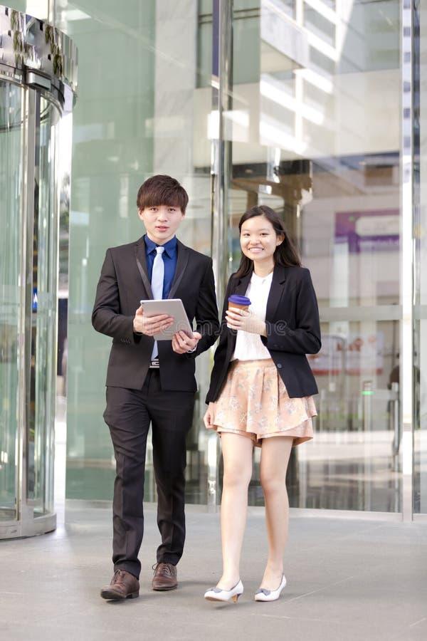Ejecutivos de operaciones asiáticos jovenes que caminan y que discuten con la tableta imagen de archivo libre de regalías