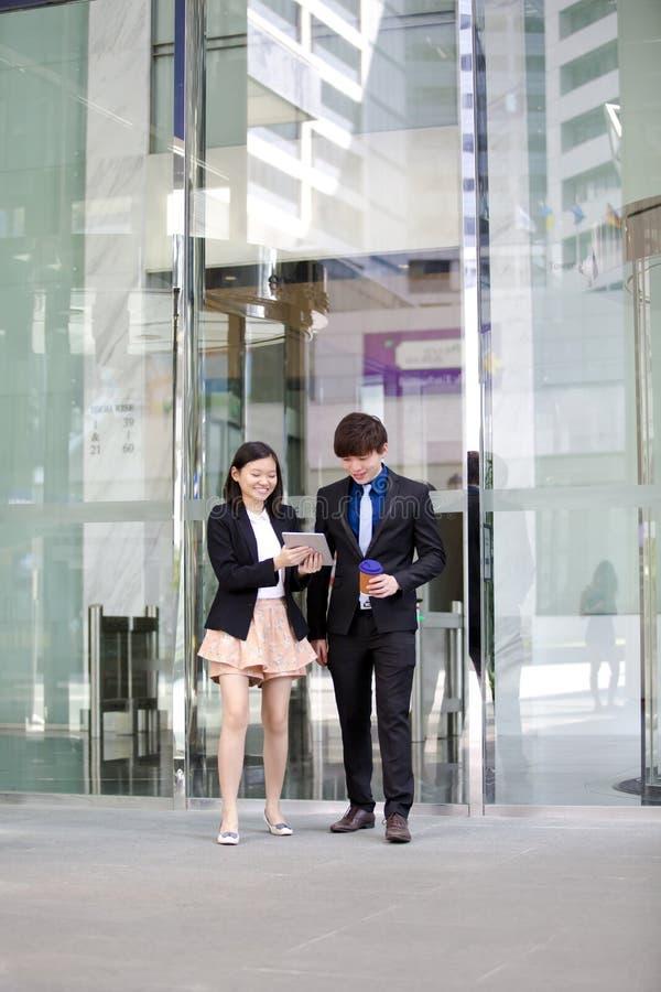Ejecutivos de operaciones asiáticos jovenes que caminan y que discuten con la tableta foto de archivo