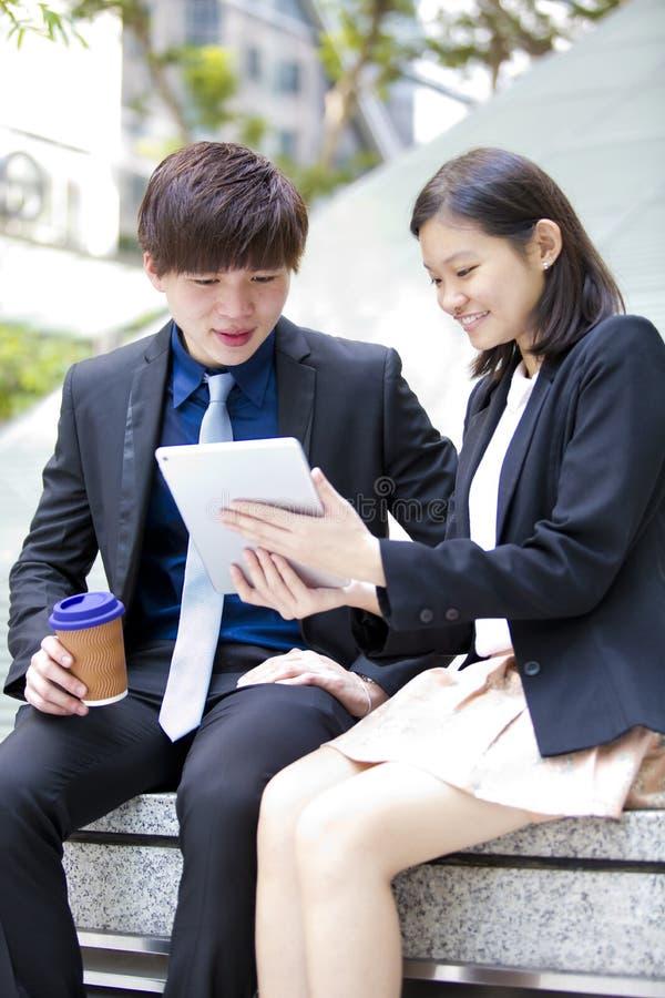 Ejecutivos de operaciones asiáticos jovenes que caminan y que discuten con la tableta fotografía de archivo