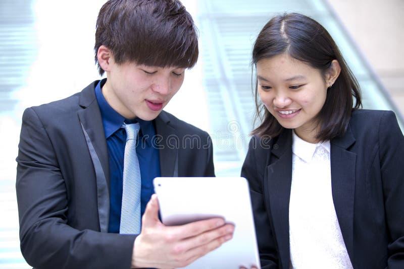 Ejecutivos de operaciones asiáticos jovenes que caminan y que discuten con la tableta foto de archivo libre de regalías