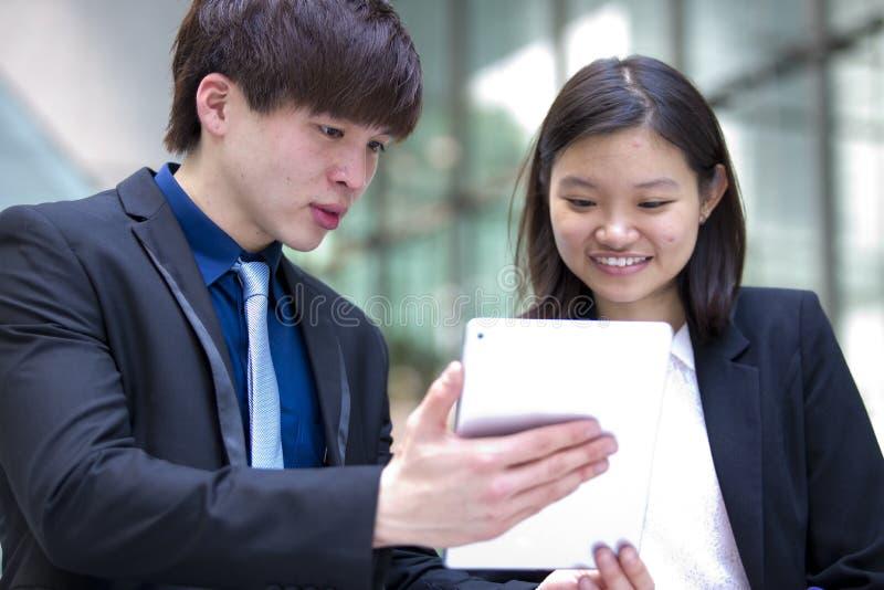 Ejecutivos de operaciones asiáticos jovenes que caminan y que discuten con la tableta fotografía de archivo libre de regalías