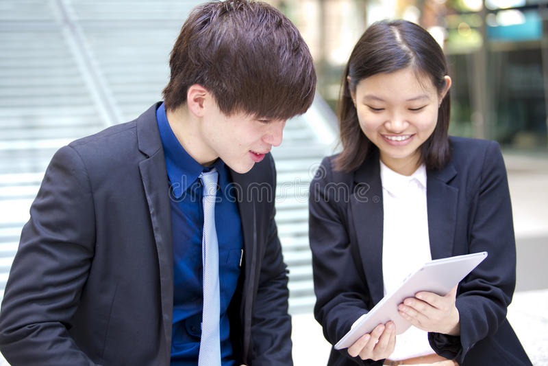 Ejecutivos de operaciones asiáticos jovenes que discuten con la tableta foto de archivo libre de regalías