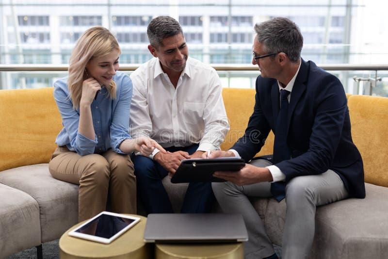 Ejecutivos de operaciones de los caucásicos que discuten sobre la tableta digital en el sofá foto de archivo libre de regalías