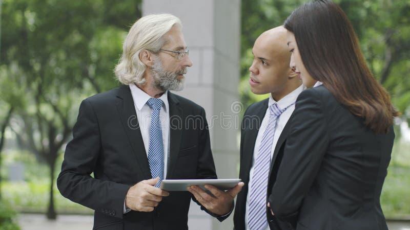 Ejecutivos empresariales que discuten negocio usando la tableta digital fotos de archivo