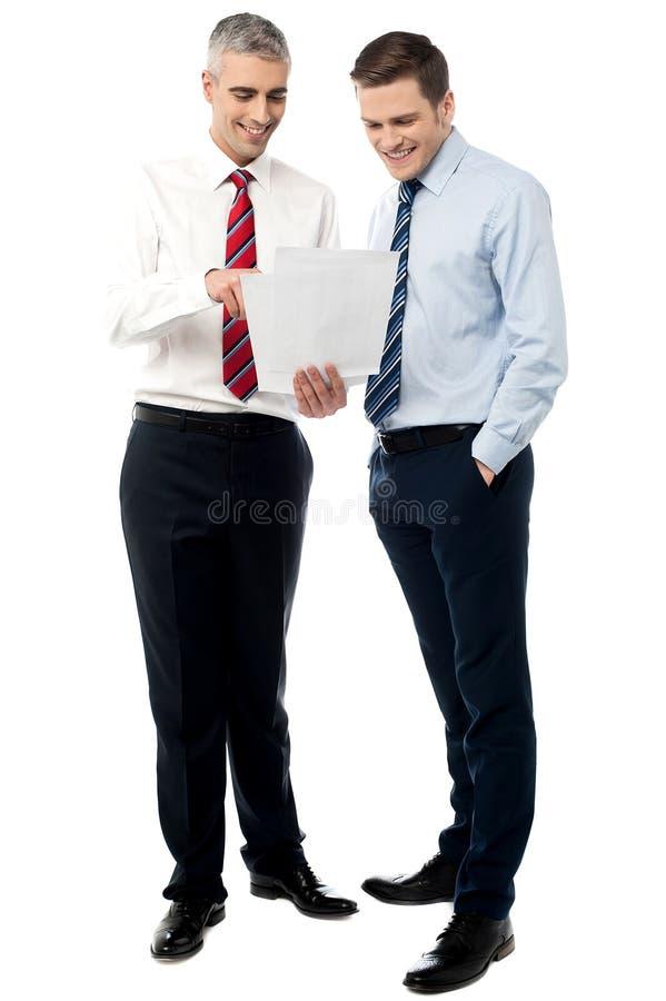 Ejecutivos jovenes que discuten informes de negocios foto de archivo libre de regalías